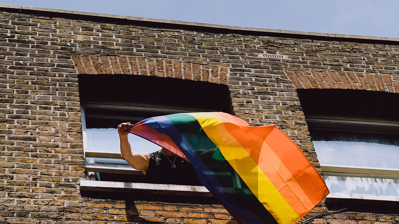 Person waving a rainbow pride flag out building window